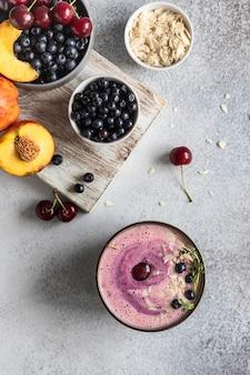 Ciotola per frullato con fette di mandorle ai mirtilli con frutti di bosco e frutta su tagliere di legno