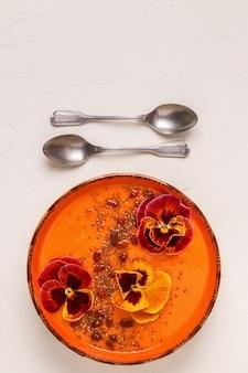 Ciotola per frullato con fiori commestibili viola del pensiero, semi di chia e bacche di goji