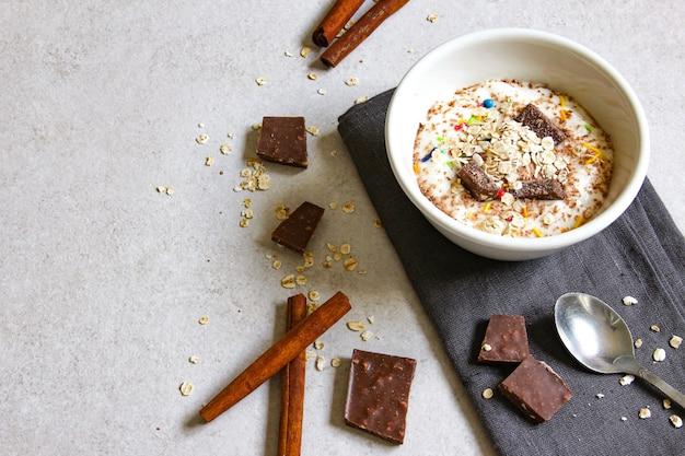 Ciotola per frullato con yogurt naturale, cioccolato e cereali su sfondo grigio colazione sana