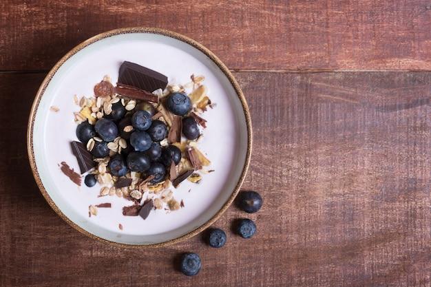 Ciotola di frullato con yogurt naturale, frutti di bosco freschi e cereali