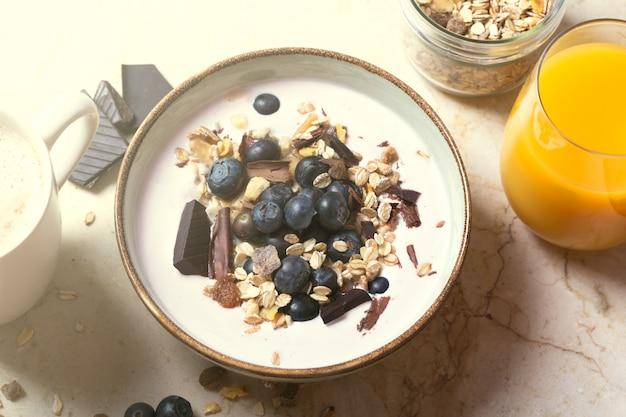 Ciotola di frullato con yogurt, frutti di bosco freschi e cereali