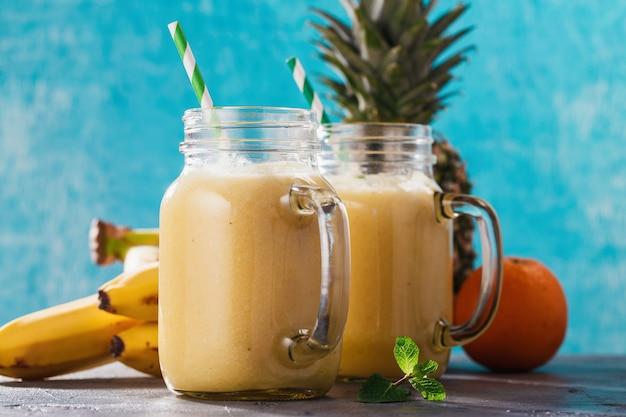 Frullati di ananas, banana e arancia in un barattolo di vetro
