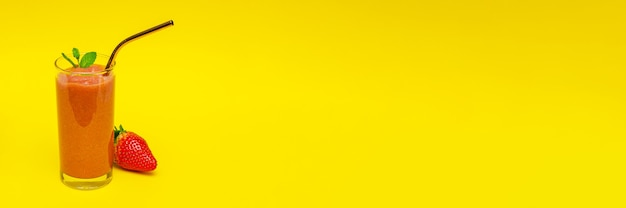 Frullati con fragole in un bicchiere di vetro, su uno sfondo giallo con spazio per le copie, il concetto di uno stile di vita sano e una dieta