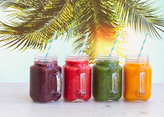 Bevande frullate in barattoli di vetro sul tavolo bianco sotto l'albero di plam