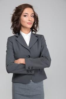 Compiaciuto presuntuoso assicurato giovane donna d'affari riccia di successo in abito grigio con le braccia incrociate