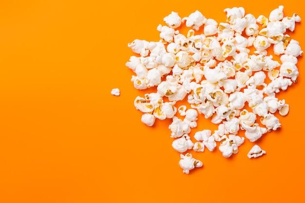 Merendina. popcorn su sfondo arancione. fai uno spuntino con il tuo film preferito, pubblicità