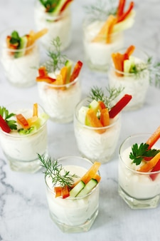 Spuntino in un bicchiere con panna fresca e verdure varie su uno sfondo chiaro.