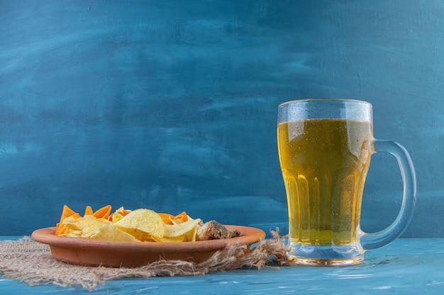 Piatto snack e boccale di birra, sullo sfondo blu.
