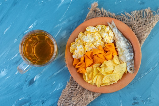Piatto snack e boccale di birra, sulla superficie blu.