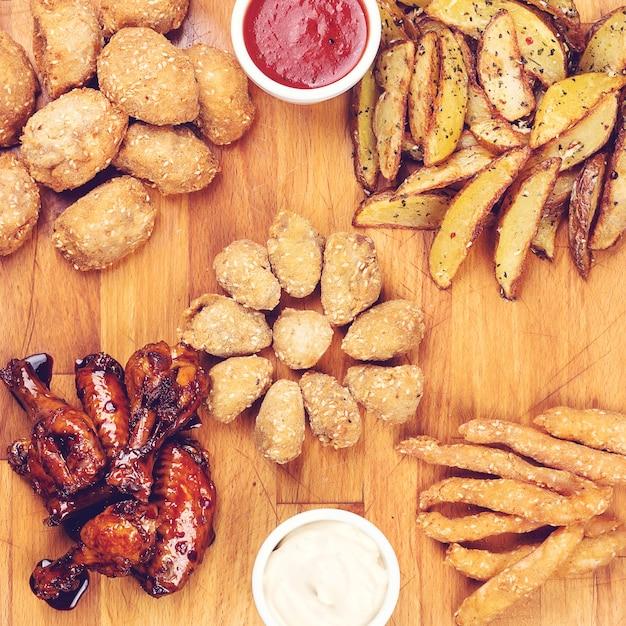 Spuntini per birra su tavola di legno. alette di pollo in stile bufalo. spuntini di carne arrosto. un grande set di snack, vista dall'alto. servizio elegante.