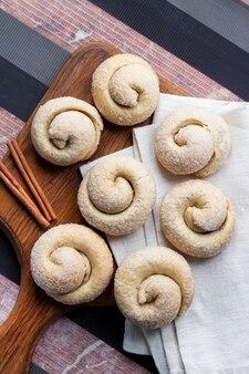 Biscotti di zucchero di lumaca con cannella su tavola di legno
