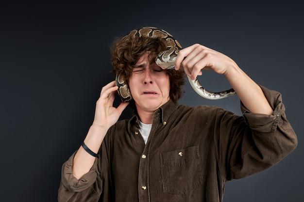 Serpente è salito sulla testa dell'uomo, l'uomo è ancora più spaventato, sente il pericolo, è spaventato e spaventato, terrorizzato
