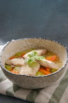 Porridge di pesce snakehead condita con coriandolo in una ciotola sul tavolo grigio.