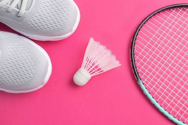 Sneakers, racchette da badminton e volano su un rosa brillante.