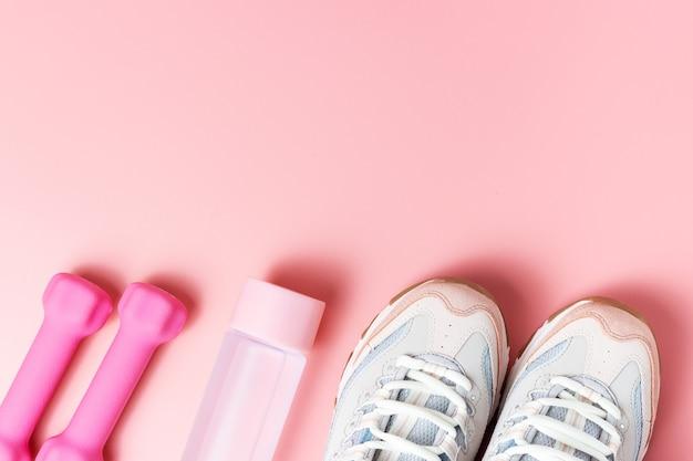 Scarpe da ginnastica, manubri su una vista dall'alto di sfondo rosa