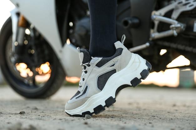 Scarpe da ginnastica su gambe femminili sullo sfondo della moto si chiuda