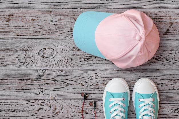 Scarpe da ginnastica, cuffie e un berretto su un pavimento di legno. stile sportivo. lay piatto. la vista dall'alto.
