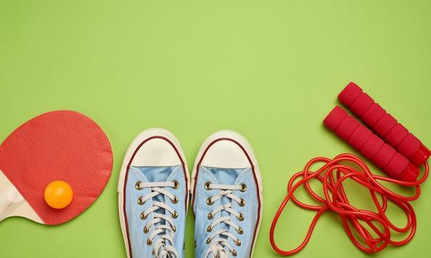 Scarpe da tennis, corda per saltare e racchette di legno per tennis da tavolo su uno sfondo verde