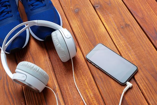 Scarpe da tennis e telefono cellulare con le cuffie sulla tavola di legno