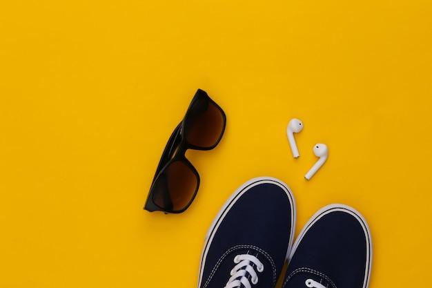 Scarpe da ginnastica e auricolari wireless, occhiali da sole su sfondo giallo.