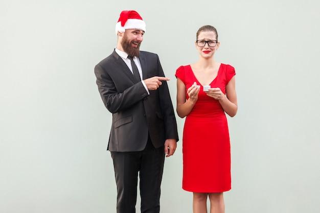 Sogghigno e concetto di finzione. uomo che punta il dito contro la donna e sorride. donna che piange e tiene un cattivo regalo. foto in studio