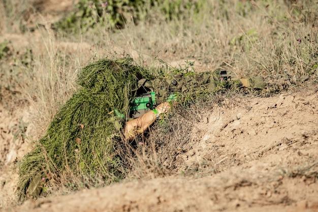Sniper armato di grosso calibro, fucile da cecchino, sparando a bersagli nemici a distanza dal rifugio, seduto in agguato.