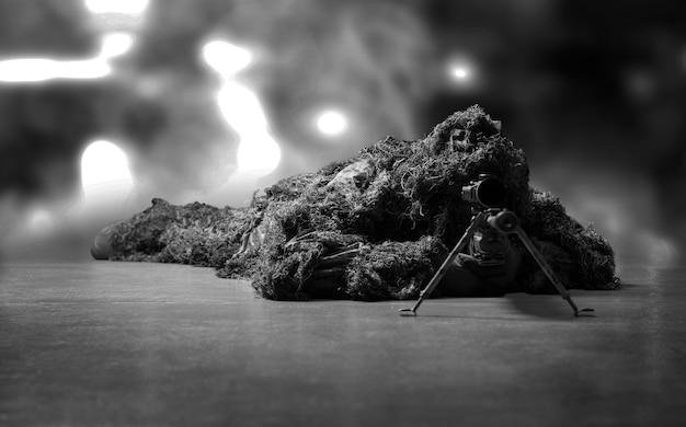 Il cecchino travestito giace con un fucile da cecchino e mira al mirino telescopico. tecnica mista