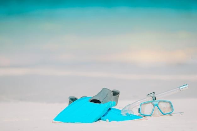 Maschera, boccaglio e pinne dell'attrezzatura per lo snorkeling sulla spiaggia bianca