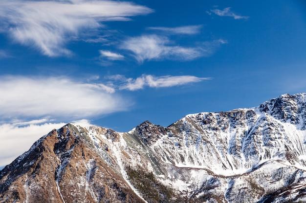 Picco di montagna innevato, ghiacciaio contro cielo blu