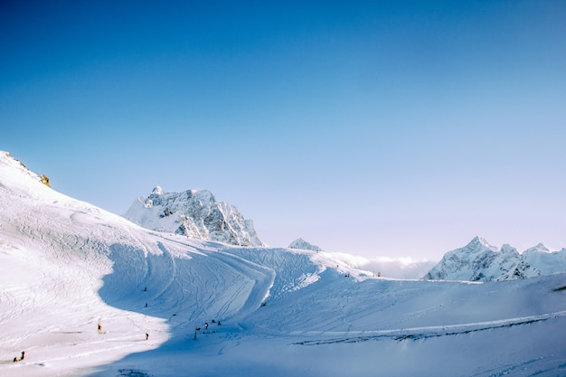 Montagne innevate in una giornata di sole in inverno. pista per sciatori e snowboarder. il concetto di sport invernali