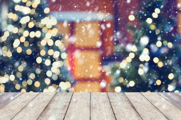 La neve sul fondo di festa di natale con il piano d'appoggio di legno vuoto sopra la luce festiva del bokeh decora sull'albero di natale. per creare la visualizzazione del prodotto di montaggio