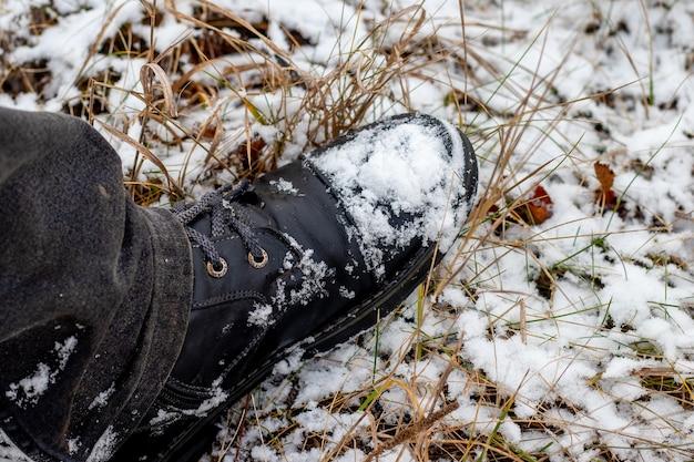 Stivale nero coperto di neve di un uomo in piedi mentre si cammina in un parco invernale, vista dall'alto. uomo in stivali neri nella neve
