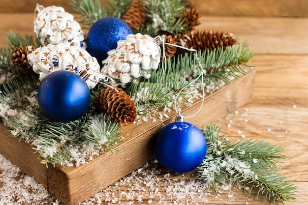 I rami coperti di neve mangiavano con coni e giocattoli di natale in una scatola di legno sul tavolo del villaggio.