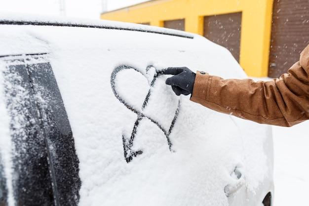 Un'auto coperta di neve si trova sulla strada in inverno. neve sui finestrini delle auto. cuore dipinto nella neve sul finestrino dell'auto