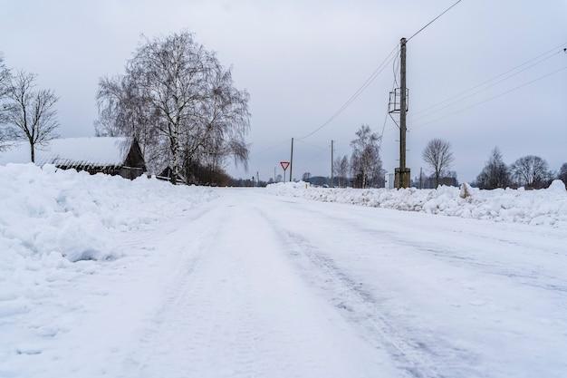 Strada di campagna innevata con mucchi di neve sui lati a basso angolo di tiro