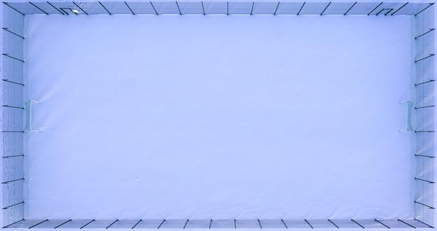 Campo di calcio vuoto coperto di neve o campo sportivo, vista aerea