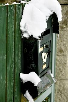 Vecchia cassetta postale rurale congelata innevata sulla porta di legno verde del paese. orario invernale europeo