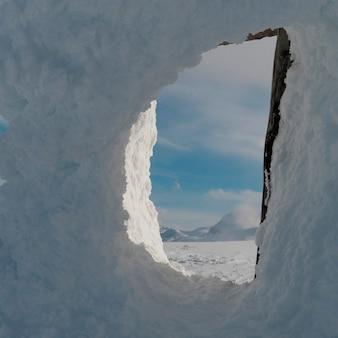 Montagne innevate osservate attraverso un inuksuk innevato, whistler, columbia britannica, canada