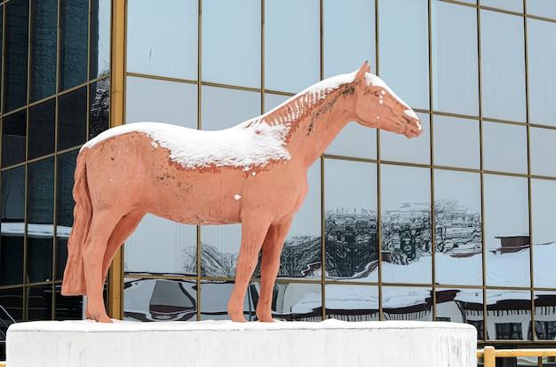 Coperta di neve scultura di cavallo nel parco cittadino con una facciata in vetro di grattacieli riflessi di altre case. simbolo della zootecnia a vdnkh.