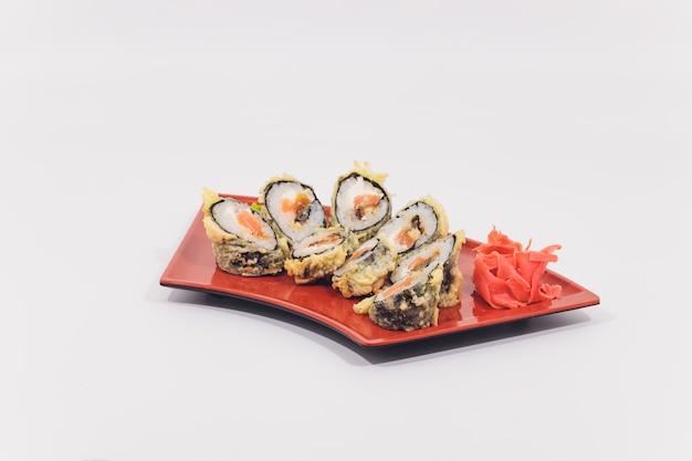 Rotoli del granchio della neve, del salmone, del formaggio cremoso e del cetriolo isolati su fondo bianco.
