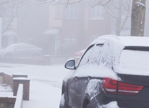 Neve sul corpo macchina scura da vicino al giorno di inverno nevoso e nebbioso.