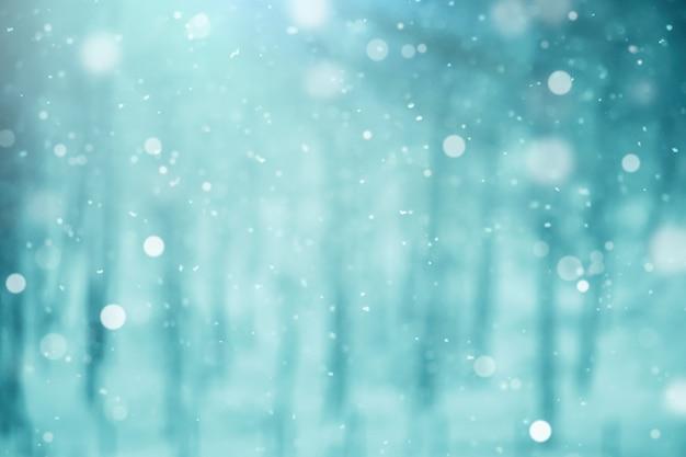 Fiocchi di neve su uno sfondo blu sfocato. luci sfocate, paesaggio invernale.