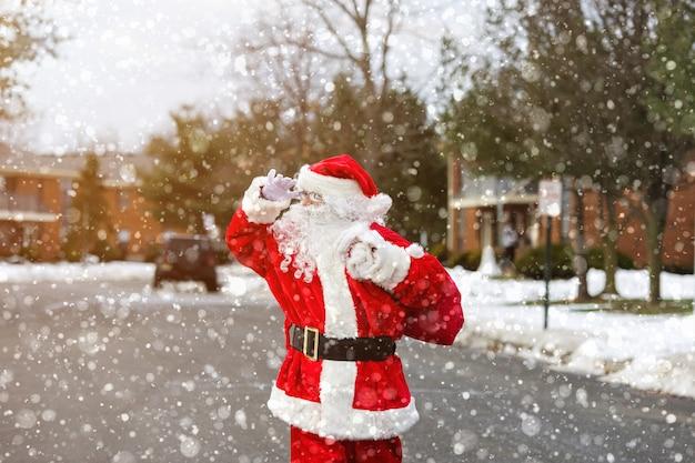 Paesaggio innevato babbo natale che trasporta una borsa pesante ai bambini che camminano lungo la strada durante una nevicata