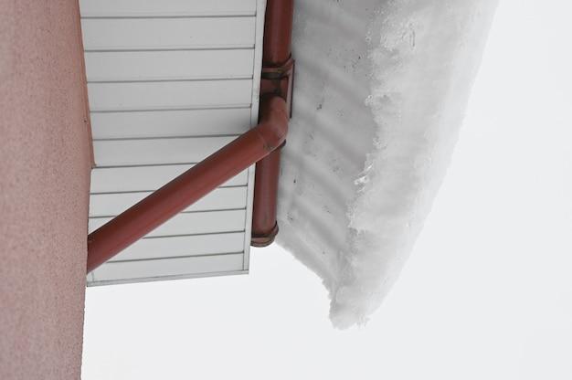 La neve sporge dal tetto della casa. deriva di neve sul tetto dopo le nevicate.