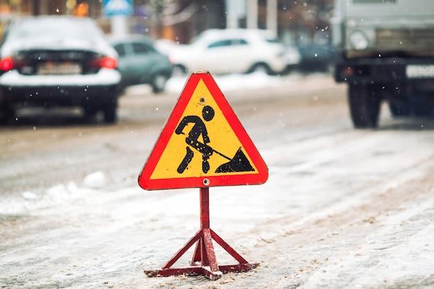 Lo spazzaneve rimuove la neve dalla via della città. segnale stradale d'avvertimento.