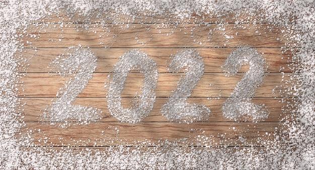 Testo 2022 a forma di neve con sfondo in legno