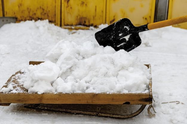 Spalare la neve con una slitta dopo una nevicata nel vialetto vicino ai garage.