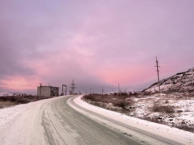 La neve gira sulla strada che si estende in lontananza tra le colline. penisola di kola. il magico colore viola dell'alba.