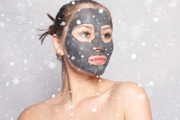 Neve, inverno, natale, persone, concetto di bellezza: maschera viso donna. ritratto di una bella ragazza che rimuove la maschera peeling nera cosmetica dalla pelle del viso su sfondo di neve