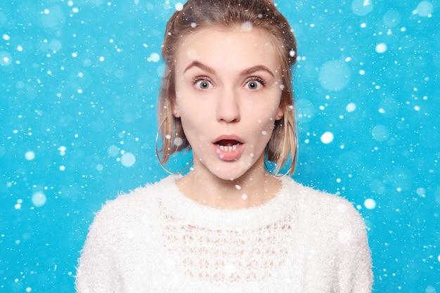 Neve, inverno, natale, persone, bellezza e concetto di stile di vita - bella donna felice sorpresa che guarda con eccitazione. su sfondo di neve